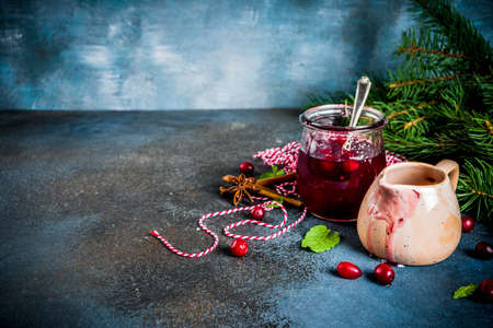 Traditional Thanksgiving Christmas food, homemade cranberry sauce, with mint and fresh berries, dark blue table, with  fir tree and saucer, copy space for text