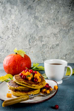 Autumnal breakfast idea, pumpkin pancakes, with slices of pumpkin, maple syrup or honey, cranberry, on a blue concrete background, space for text