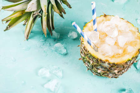 Summer refreshment drink concept, tropical pineapple cocktail or juice in pineapple with ice, light blue concrete background copy space
