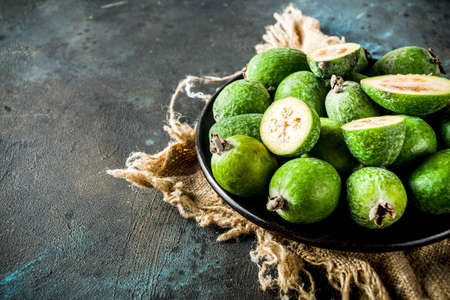Tropical fruit, raw organic feijoa on a dark blue concrete background, copy space