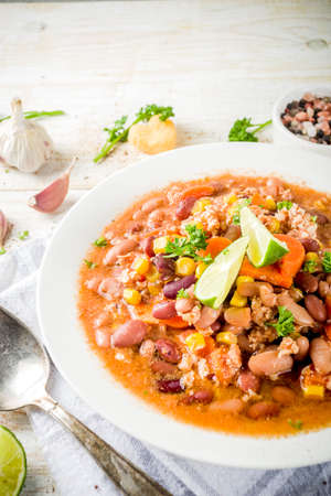Chili con carne in plate on white wooden background. Mexican chili with meat, nachos, lime, hot pepper. Mexican and american texas traditional food, top view copy space Stock Photo