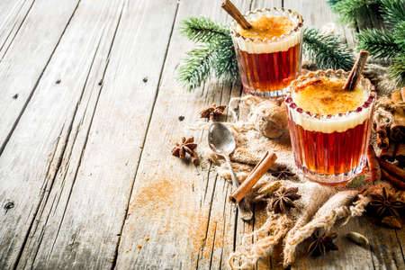 Winter holidays traditional drink, homemade hot buttered rum with spices, over old rustic wooden background with christmas tree branches, copy space Stock Photo