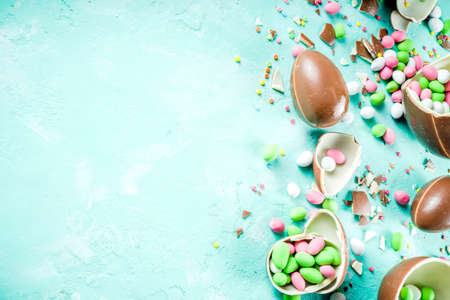 Colorful spring easter sweets background, with chocolate eggs, sugar sprinkles and marshmallow bunny, turquoise light blue concrete background copy space top view
