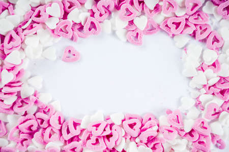 Valentines sweets background, white background with sugar hearts sweet sprinkles, copy space top view, layout on white