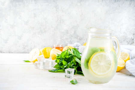 Homemade sour cocktail lemonade, with fresh lemons, mint and honey, white wooden background copy space Stock Photo