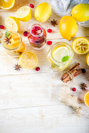 Set of various fall and winter refreshing infused water, sweet sour healthy beverages with oranges, honey, cranberry, mint, rosemary, cinnamon and spices, white wooden background copy space