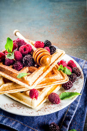 Homemade belgian waffles with berries and honey, on dark blue background copy space Stock Photo