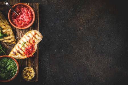 Grilled chicken breast with spicy sauces, tomatoes and herbs on dark rusty background copy space top view Banco de Imagens