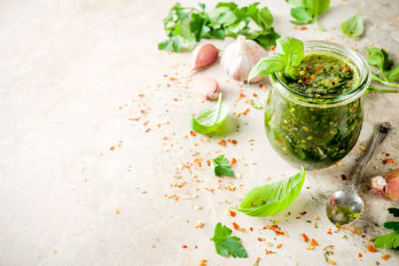 Argentinian traditional food, raw homemade green Chimichurri salsa or sauce woth parsley, garlic, basil leaves, hot pepper and spices, light stone table copy space