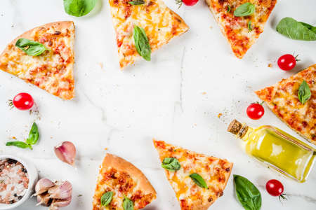 Homemade sliced cheesy classic italian pizza with ingredients and olive oil, white marble background copy space top view