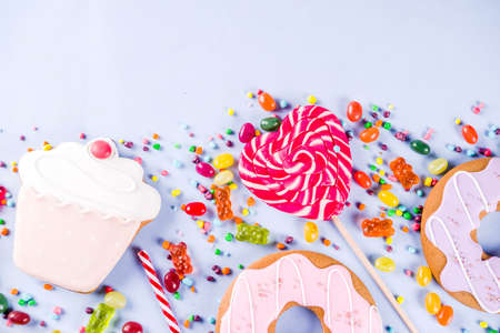 Sweets creative lay out, dessert concept with lollipops, jellies, candy, cookies donuts and cupcakes, light blue background top view copy space