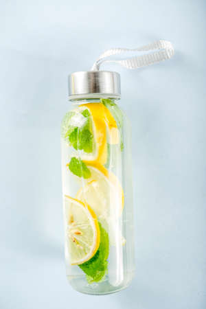 Homemade  lemonade in glass bottle, summer healthy drink concept, infused water, bright trendy background top view copy space