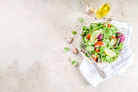 Fresh spring detox mix salad with vegetables (cucumber, lemon, tomato, arugula, and baby spinach), on light slate, stone or concrete background. Top view copy space