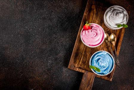 Healthy diet summer dessert, vanilla and berry frozen yogurt or  soft ice cream in white bowls, white marble background copy space above