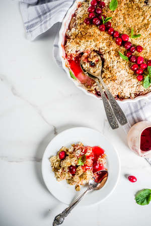 Traditional autumn winter pastries, homemade pie crumble with apples and cranberries, on a white marble table, copy space for text Stock Photo