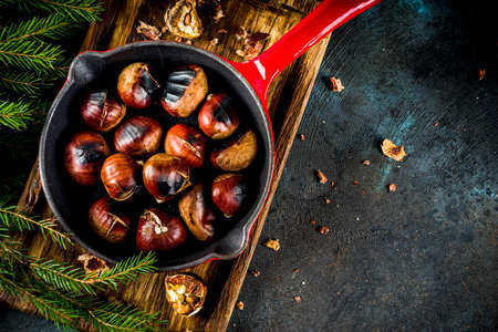 Cracked roasted chestnuts, traditional autumn winter homemade snack, on small chestnut's frying pan, copy space Stockfoto