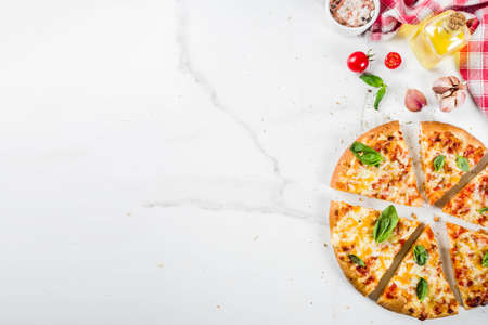Homemade sliced cheesy classic italian pizza with ingredients and olive oil, white marble background copy space top view Reklamní fotografie - 114393148