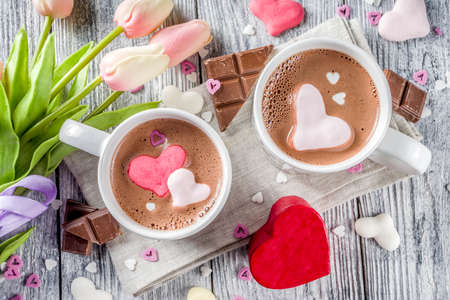 Valentines day treat ideas, two cups hot chocolate drink with marshmallow hearts red pink white color with chocolate pieces, sugar sprinkles, old wooden background copy space top view Stock Photo