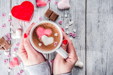 Girl hands hold hot chocolate with marshmallow hearts, red pink white color with chocolate pieces, sugar sprinkles, old wooden background copy space top view, hands in pictute flatlay Banque d'images - 114576978
