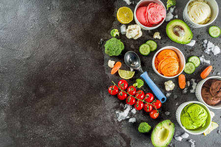 Trendy vegan food, summer healthy dessert concept, colorful diet vegetable ice cream with avocado, cucumber, tomato, beet, carrot, broccoli, cauliflower. Frozen veggie smoothie, black background