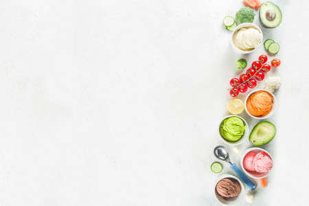 Trendy vegan food, summer healthy dessert concept, colorful diet vegetable ice cream with avocado, cucumber, tomato, beet, carrot, broccoli, cauliflower. Frozen veggie smoothie, white background