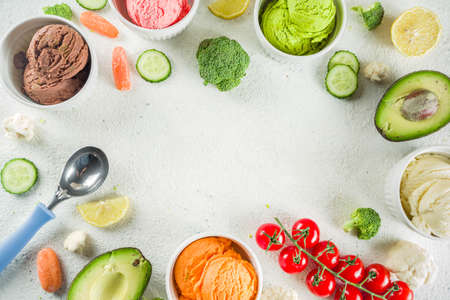 Trendy vegan food, summer healthy dessert concept, colorful diet vegetable ice cream with avocado, cucumber, tomato, beet, carrot, broccoli, cauliflower. Frozen veggie smoothie, white background