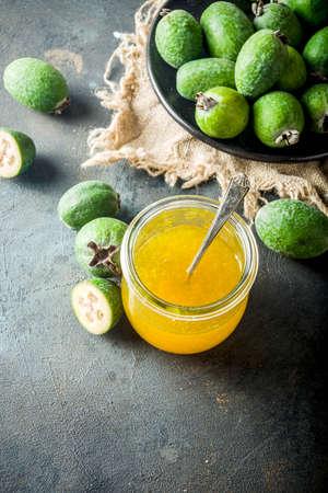 Tropical fruit preserves, homemade feijoa and lime jam on a dark blue concrete background, copy space