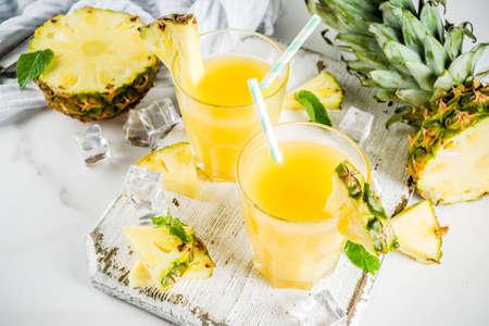 Frischer Ananassaft oder Cocktail, mit frischen Ananasstücken, Eis, dekoriert mit Minze, auf einem weißen Marmortisch, Kopierraum