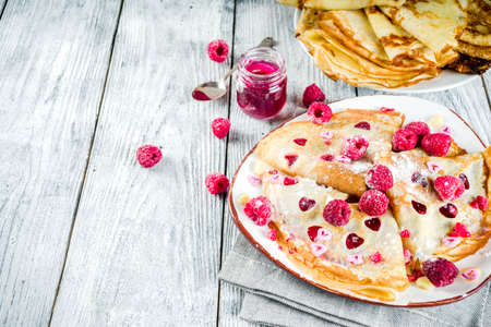 Idea for Valentines Day surprise gift. Cute pancakes crepes with berry sauce and heart shaped cutouts. Romantic valentine breakfast. On wooden table, with fresh raspberries. Copy space