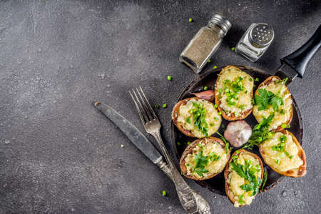 Homemade double baked loaded potato with cheese, herbs and green onions, dark background top view copy space.