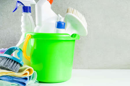 Cleaning concept with different cleaning supplies, on gray stone concrete background copy space