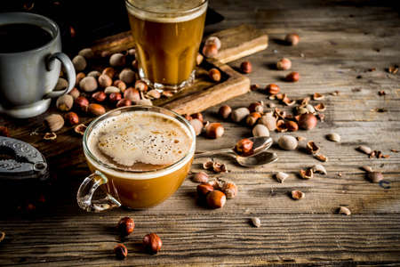Homemade hazelnut coffee latte or cappuccino, rustic wooden background with hazelnuts, three coffee cups copy space