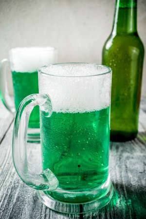 St. Patricks day concept, two glasses and bottle with cold fresh cold green beer on wooden table, bar counter Background for St. Patricks day and Oktoberfest menu. Copy space
