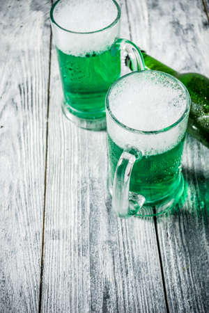 St. Patrick's day concept, two glasses and bottle with cold fresh cold green beer on wooden table, bar counter Background for St. Patrick's day and Oktoberfest menu. Copy space Stok Fotoğraf - 115416092