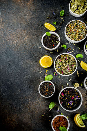 Assortment of various dry tea - classic black and green, flower, fruit, berry and herbal tea blends, with lemon and mint, White marble background copy space top view Banco de Imagens