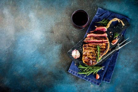 Sliced grilled roast beef with fork for meat and wine on wooden cutting board. Dark blue background. Top view copy space Stock Photo - 115475408