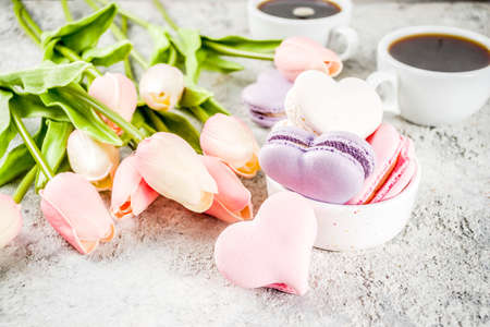 Background for greeting card Valentines holiday. Valentine days present, sweet treat. Homemade  pastel colored macaron cookies, with tulip flowers, on a light grey concrete background copy space