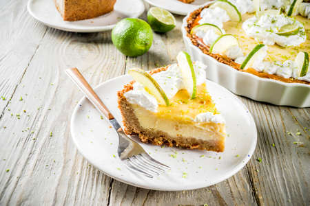 Homemade sweet cake, classic key lime pie with fresh limes, on wooden background copy space 版權商用圖片