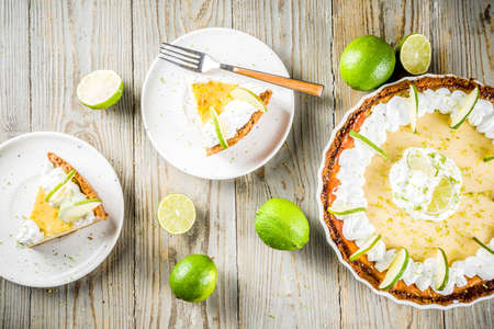 Homemade sweet cake, classic key lime pie with fresh limes, on wooden background copy space Standard-Bild