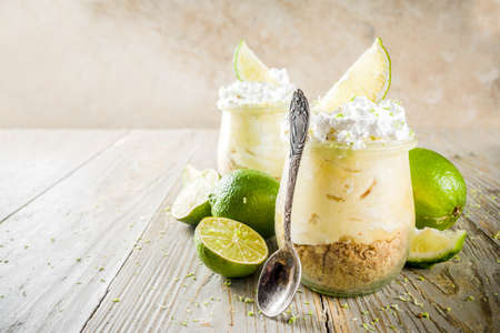 Hausgemachter nicht gebackener Käsekuchen. Key Lime Pie in kleinen Portionsgläsern, Holzhintergrund-Kopierraum