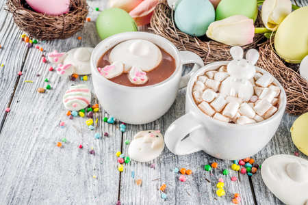 Easter funny kids food and drink concept, sweet hot chocolate with marshmallow bunny rabbits and easter eggs, wooden background copy space top view