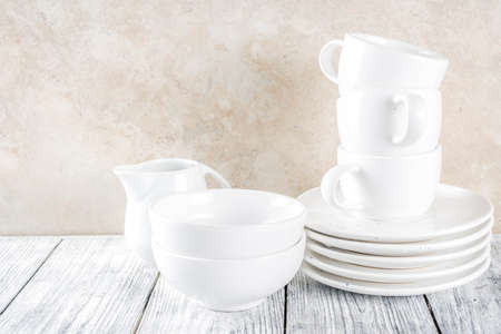 Assortment stack clean empty new white kitchen utensils, plates, bowls, cups mugs. On a white concrete background