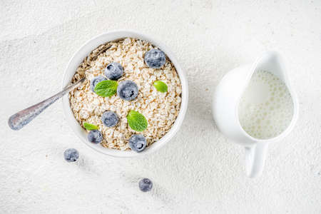 Healthy cereal and milk breakfast concept, dry oats in small bowl, with milk and fresh blueberry, white  wooden concrete background copy space