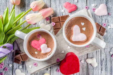 Valentines day treat ideas, two cups hot chocolate drink with marshmallow hearts red pink white color with chocolate pieces, sugar sprinkles, old wooden background copy space top view Stock fotó