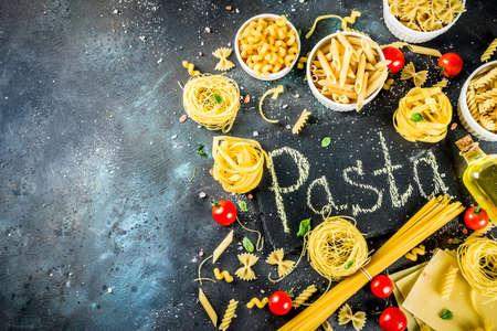 Italian food concept, various raw pasta assortment - spaghetti, lasagna, fusilli, tagliatelle, penne, tortellini, ravioli, with tomatoes and basil leaves dark background copy space top view