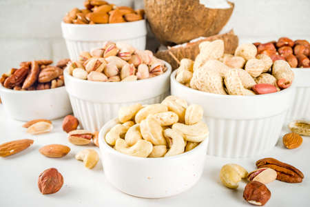 Various types of nuts - walnuts, pecans, peanuts, hazelnuts, coconut, almonds, cashews, in bowls, on a white marble table top view