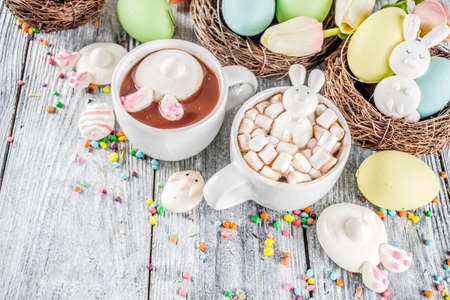 Easter funny kids food and drink concept, sweet hot chocolate with marshmallow bunny rabbits and easter eggs, wooden background copy space top view Stock Photo - 116047751