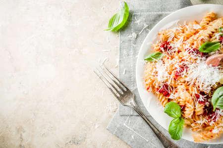 Comida italiana, pasta fusilli con salsa de tomate, queso parmesano rallado y albahaca, mesa de piedra clara copia vista superior del espacio Foto de archivo