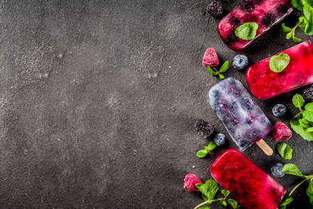 Simple and healthy summer dessert. Homemade berry ice cream   with mint. Mojito lollypops, frosen diet infused water with blackberry, blueberry and raspberry. Dark concrete background copy space top view 版權商用圖片