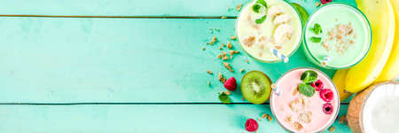 Summer refreshing drinks - protein shakes, milkshakes or smoothies, with fresh berry and fruits, light blue table copy space banner Stock Photo